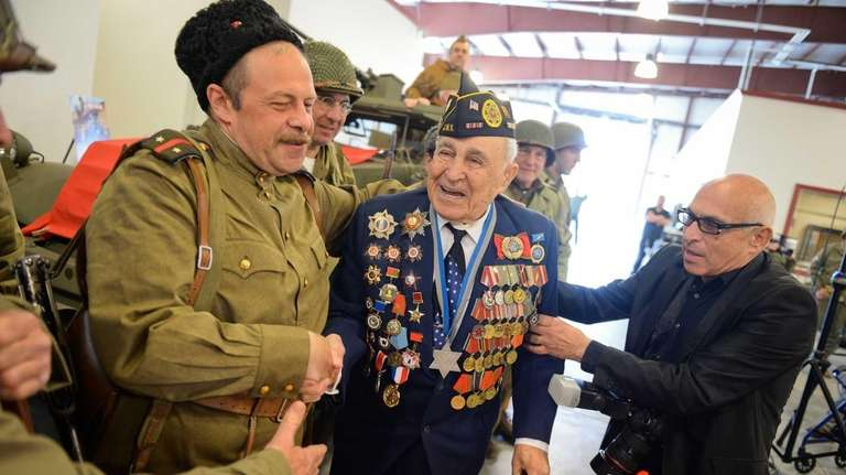Leonid Rosenberg, of Brooklyn, greets reenactors during a