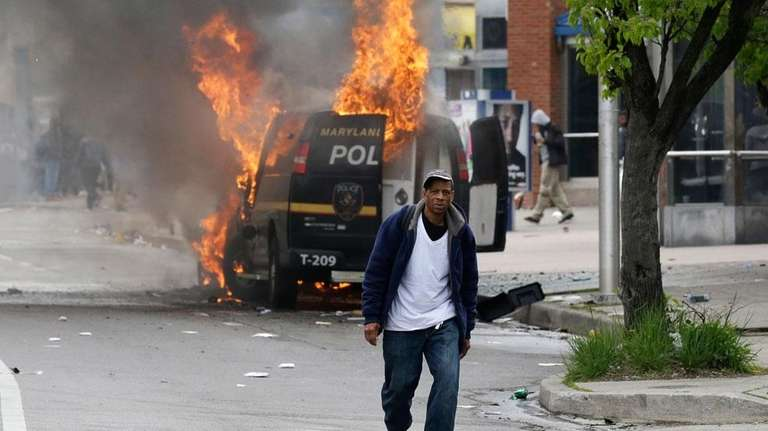 A man walks past a burning police vehicle,