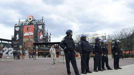 Baltimore police officers stand guard outside of Oriole