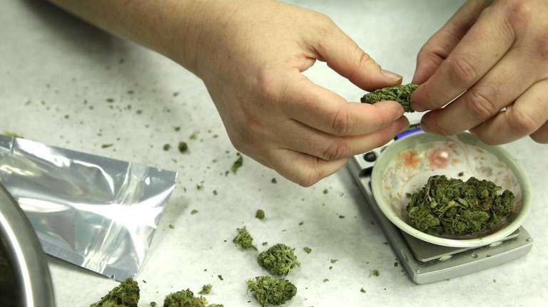 A file photo shows marijuana being weighed and
