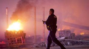 A police officer walks by a blaze, Monday,