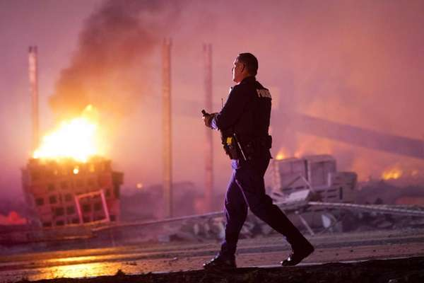 A police officer walks by a blaze, Monday,