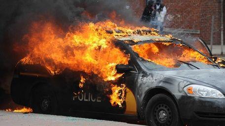 An officer vehicle burns Monday, April 27, 2015,