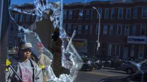Residents, reflected off broken glass, clean up after