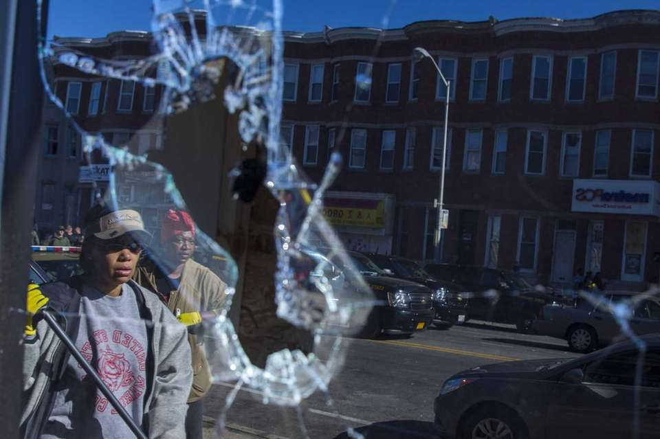 Residents, reflected off broken glass, clean up on