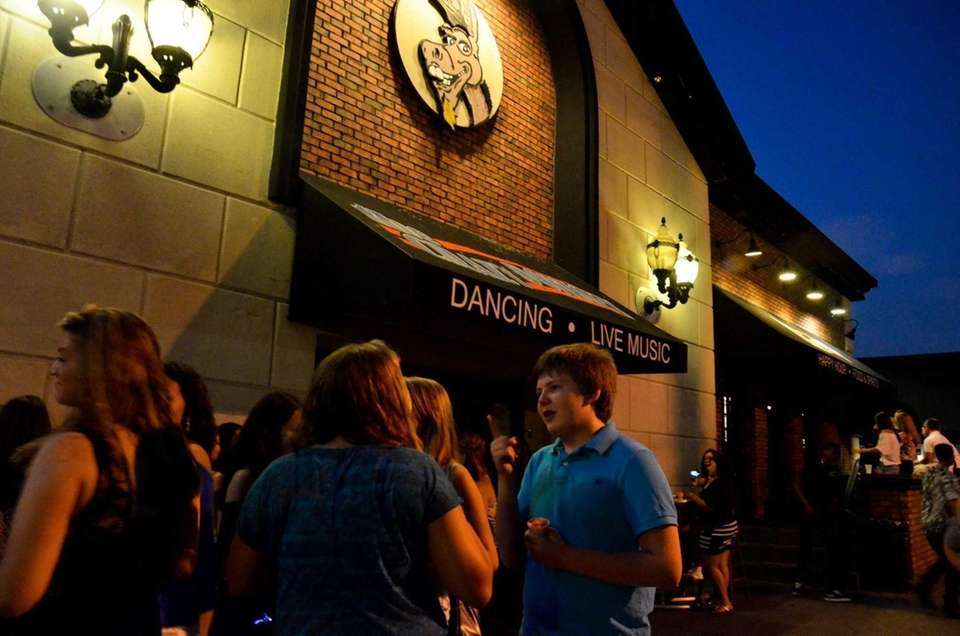Teens hang outside the Crazy Donkey in Farmingdale