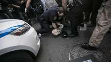 A protester is arrested during a rally in