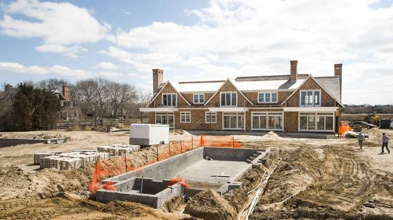 Construction workers build an 8,600-square-foot, nine-bedroom spec home