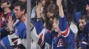 Rangers fans bang on the glass during pregame