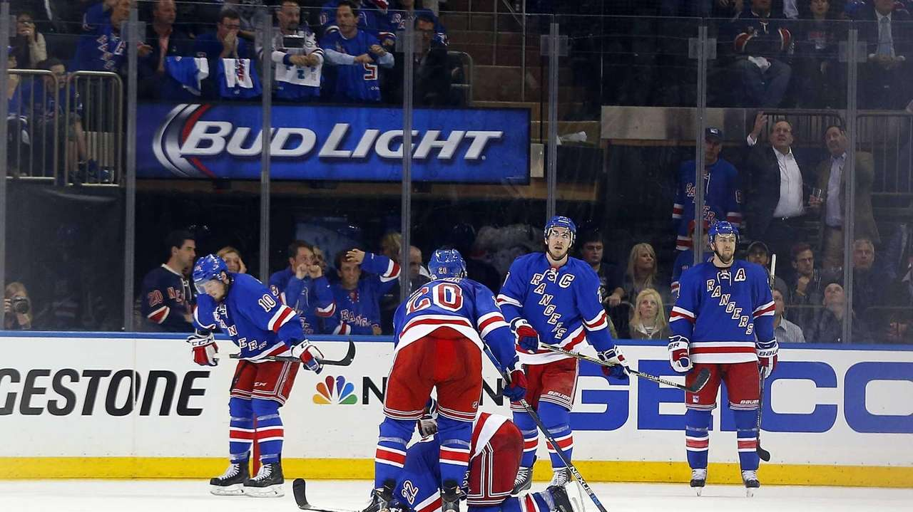 Members of the New York Rangers look on