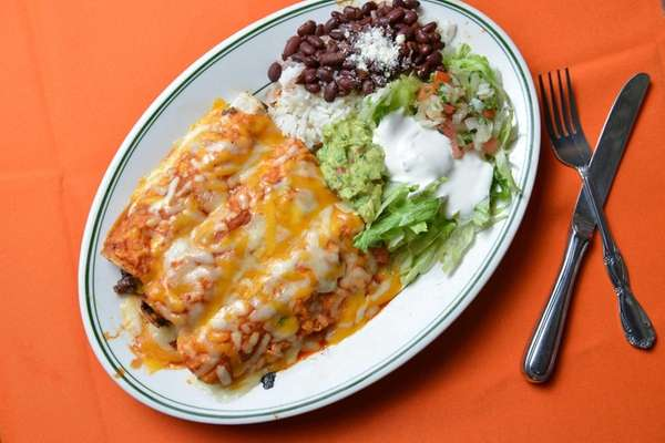 Beef enchiladas served with rice and beans, guacamole,