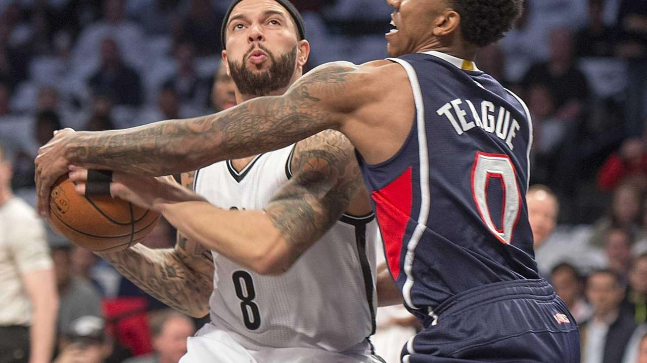 Brooklyn Nets' Deron Williams is trapped by Jeff