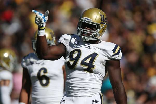 UCLA defensive lineman Owamagbe Odighizuwa gestures to teammates