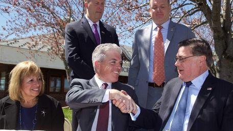 Suffolk County Executive Steve Bellone, center, shakes hands