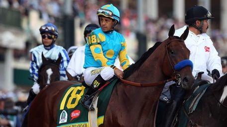 Jockey Victor Espinoza guides American Pharoah #18 on