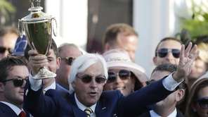 Trainer Bob Baffert holds up the winning trophy