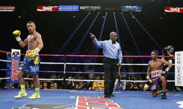 Vasyl Lomachenko, left, of the Ukraine is sent