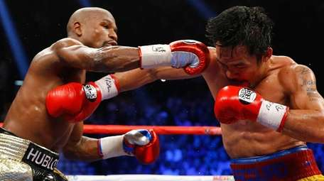 Floyd Mayweather Jr., left, exchanges punches with Manny
