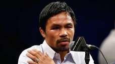 Manny Pacquiao points to his right shoulder during