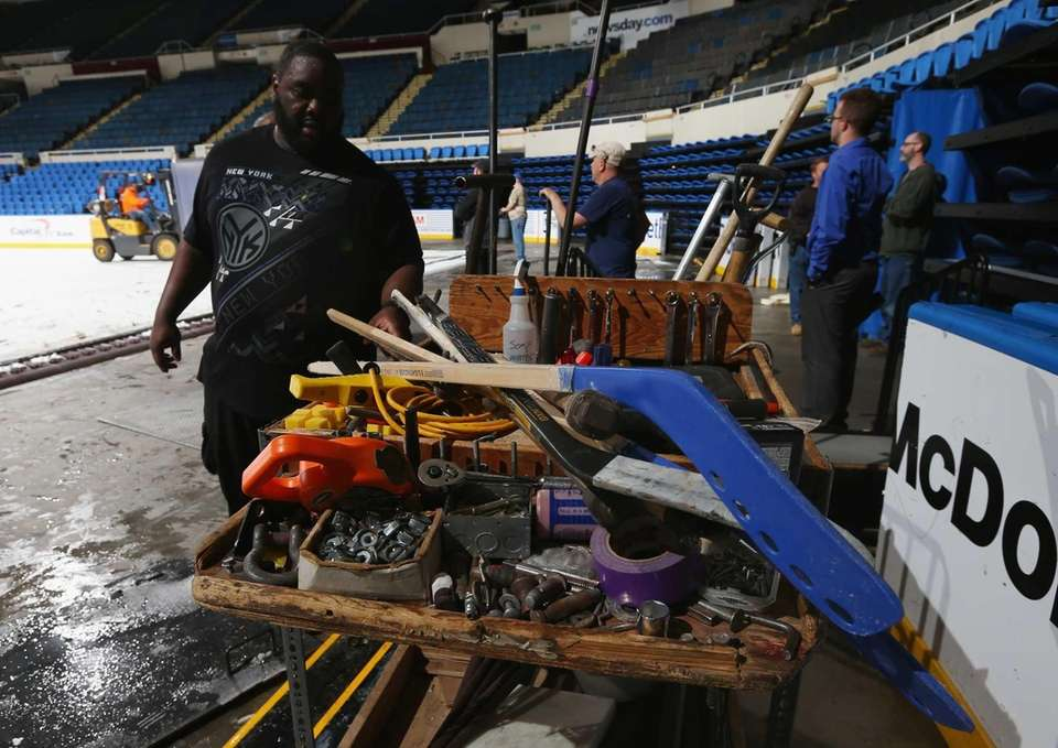 An arena worker picks out tools to assist