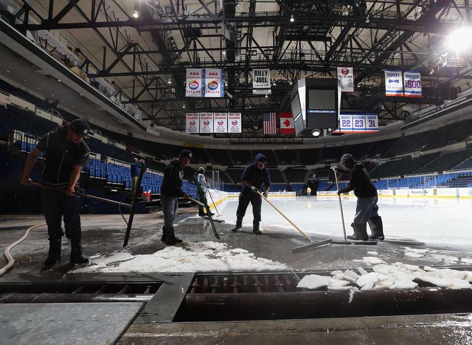 Arena workers remove the rink and ice from