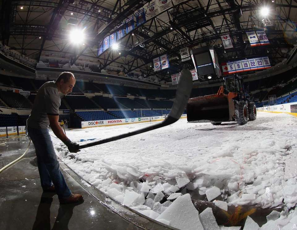 An arena worker uses a hockey stick to