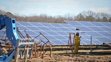 Workers perform maintenance on the panels at the