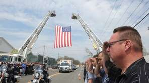 Police officers and firefighters salute as an ambulance,