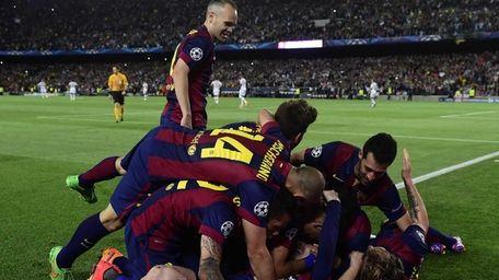 Barcelona midfielder Andres Iniesta, top left, celebrates with
