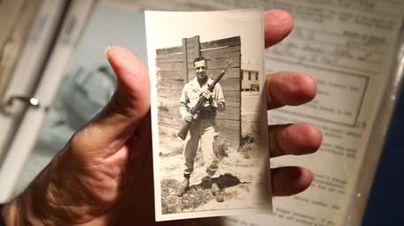 U.S. Army veteran Ernest Marano holds a photograph