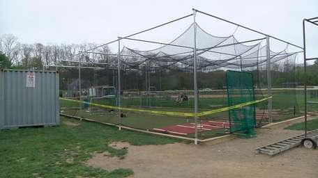 Police tape surrounds a Little League practice cage