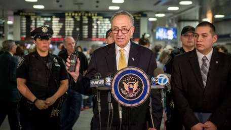 U.S. Senator Charles E. Schumer, center, urges the