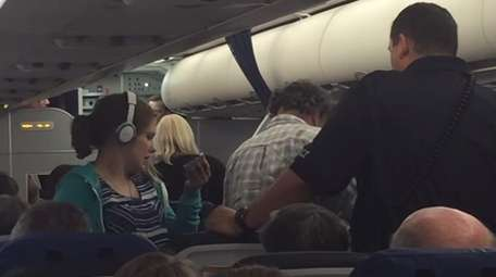 Passengers on a United Airlines plane gather after