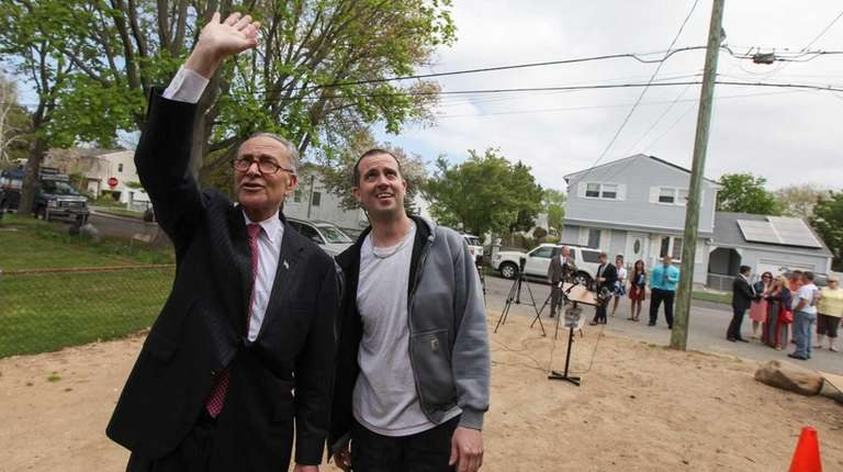 Sen. Charles Schumer, left, greets a contractor working