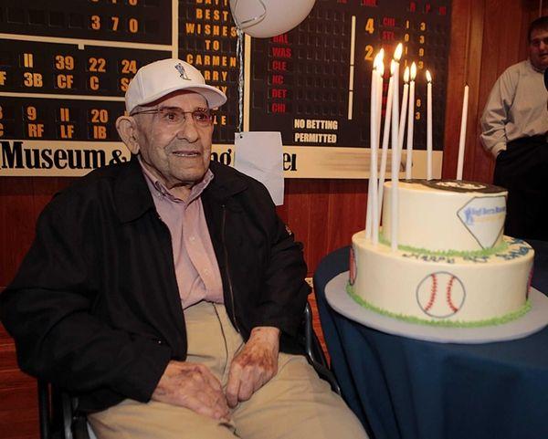 Yogi Berra poses with his 90th birthday cake
