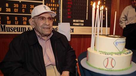 Yogi Berra poses with his 90th birthday cake