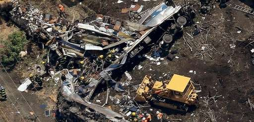 Investigators and first responders work near the wreckage