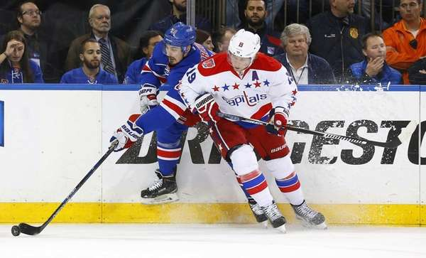 Nicklas Backstrom of the Washington Capitals defends against