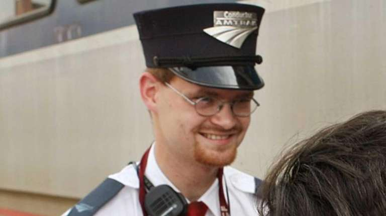Amtrak assistant conductor, Brandon Bostian stands by as