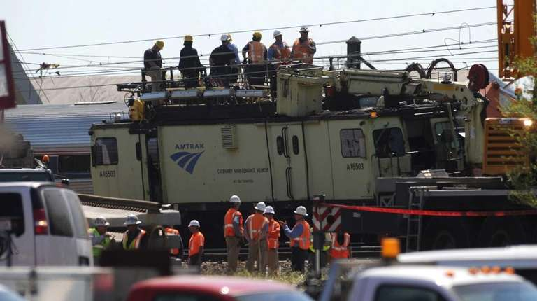 Amtrak crews work at the site of the