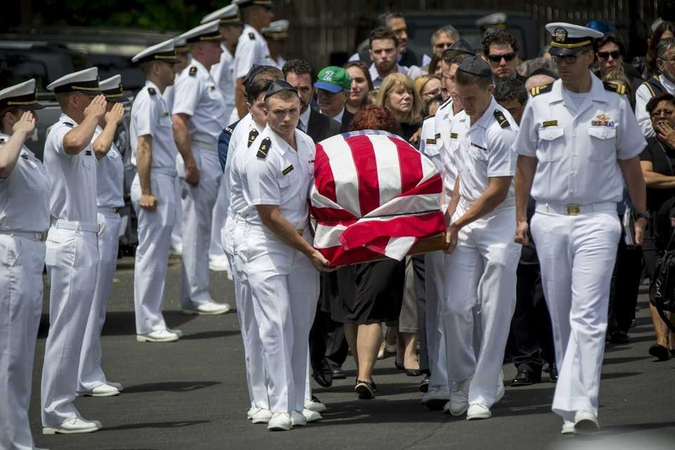 Pallbearers carry the coffin of U.S. Naval Academy