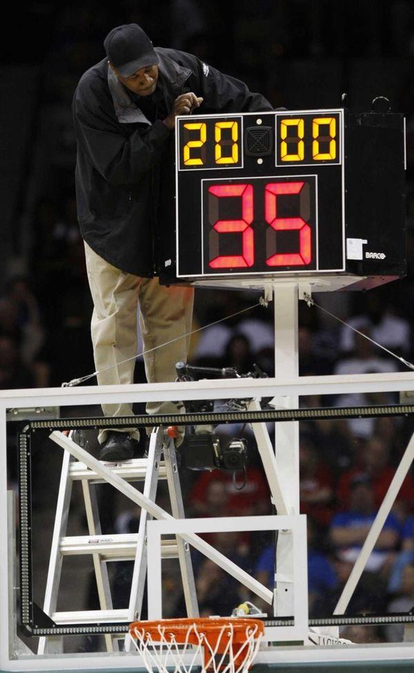 A technician adjusts a shot clock after it