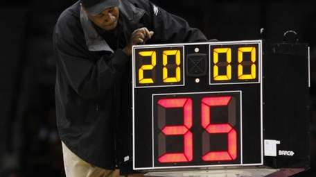 A technician adjusts a shot clock after it