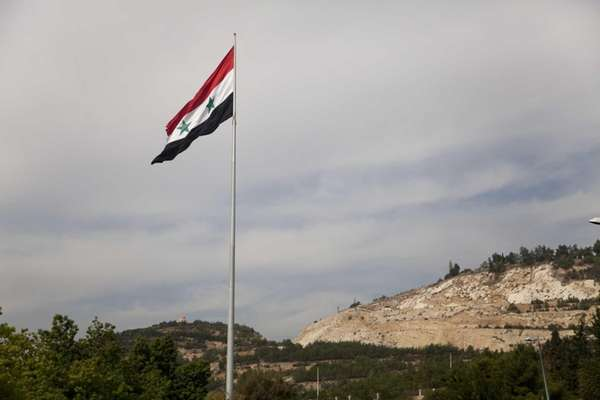 A Syrian flag flies over the capital, Damascus,