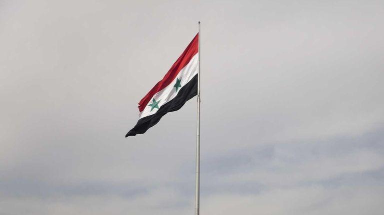 A Syrian flag flies over the capital, Damascus,