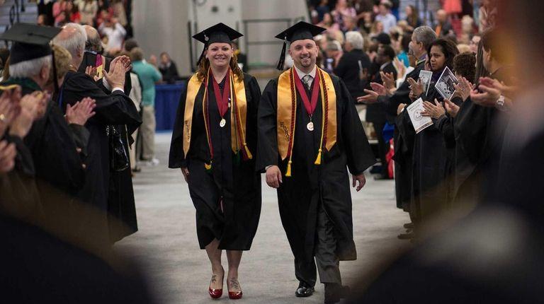 Valedictorians Suzanne Calderia and Joseph Messa walk at