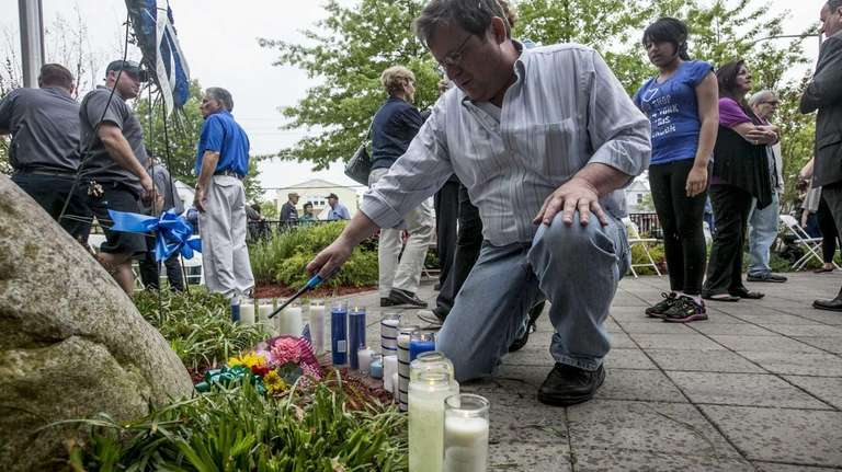 A man lights a candle at a tribute