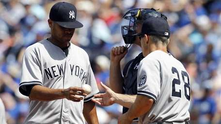 New York Yankees pitcher Esmil Rogers, left, hands