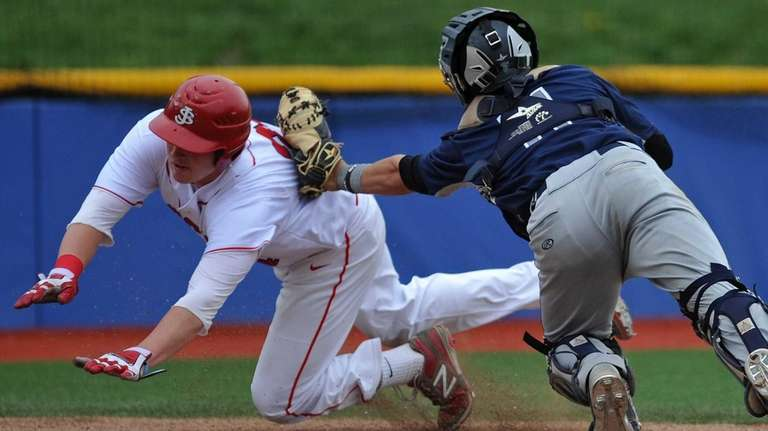 St. Dominic catcher Greg Tan, right, tags out
