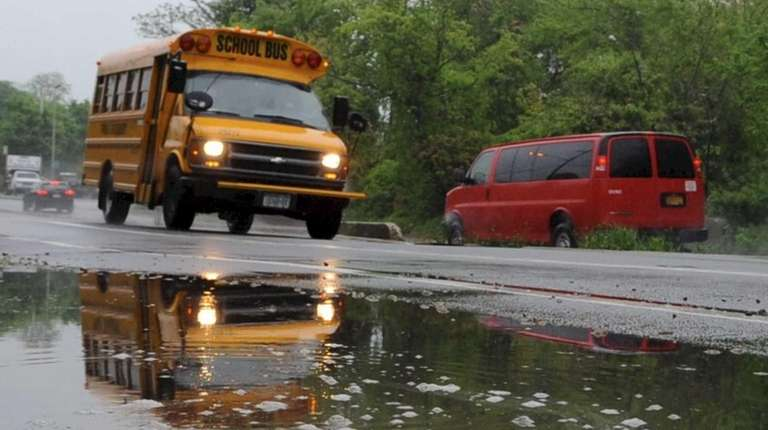 A school bus drives by a puddle on